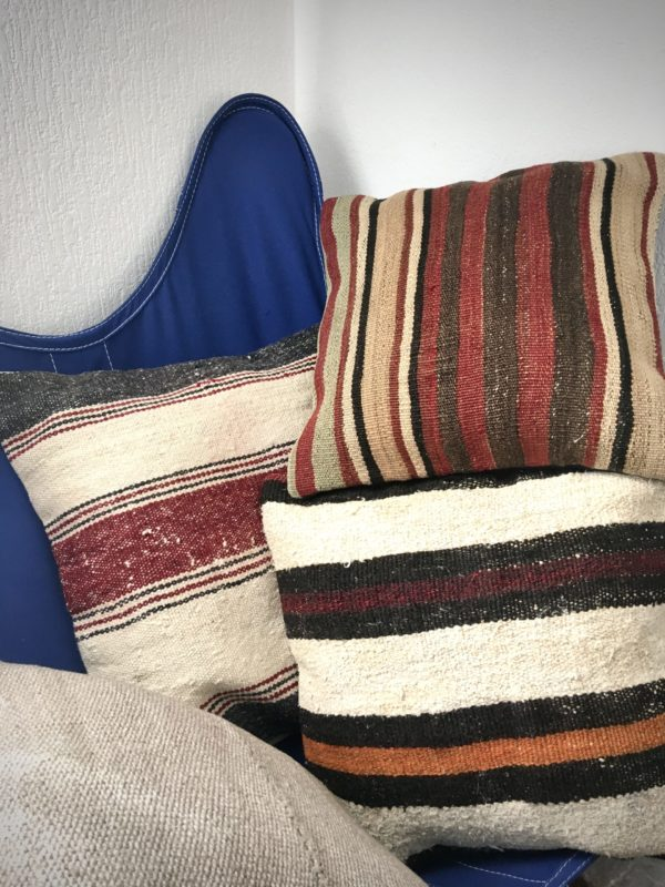 square wool kilim pillows in beige tone with stripes red, orange, burgundy, brown on a AA outremer chair