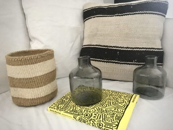 square beige wool kilim cushion #7 with a sisal basket with natural and beige large stripes and upcycled glass grey carafes