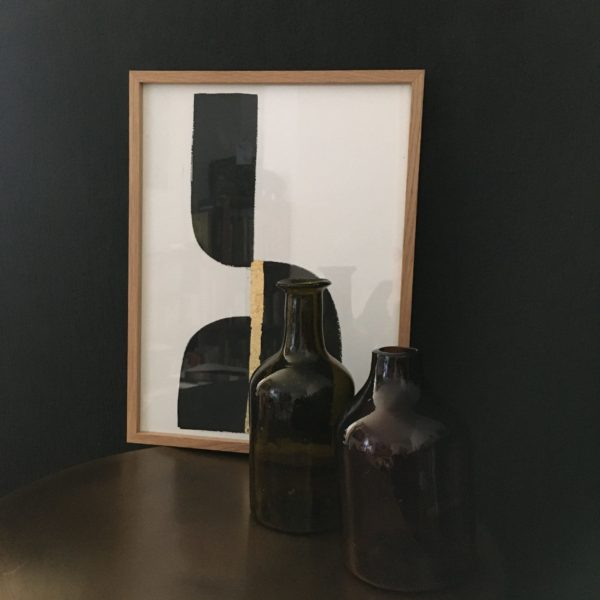 India ink #2 and amber recycled glass carafes on a black wall