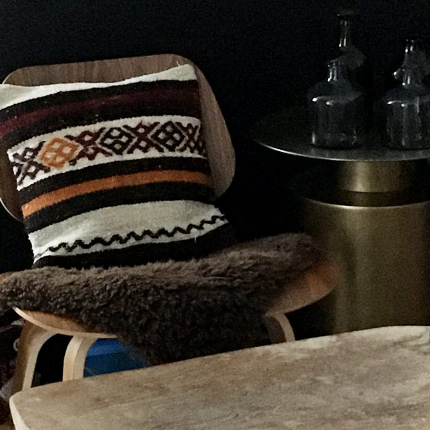 kilim cushion #6 on a LCW chair with a dark brown sheep skin and grey and amber up cycled handblown carafes